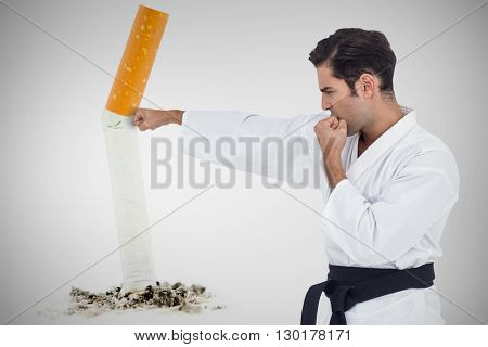 Fighter performing karate stance against image of pressed cigarette on a white background