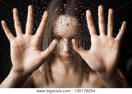 Lonely women with outstretched hand. In the glass.