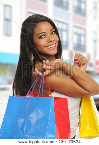 Young black woman with shopping bags outside a mall