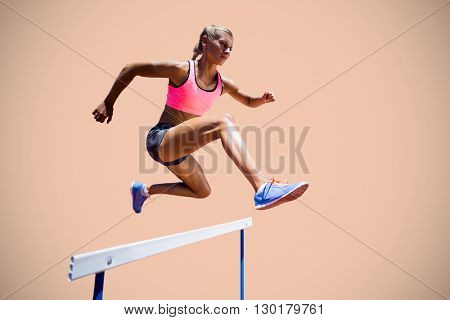 Sporty woman jumping a hurdle against beige background