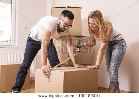 Young girl moving in a new apartment with her boyfriendstanding surrounded with cardboard boxes packing and taping boxes while the boyfriend carries boxes away