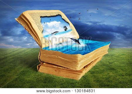 Concept of reading. Opened magic book with torn page.Dolphin jumps out of the page into water sailing ship on the horizon birds fly away. Concept of dreaming.