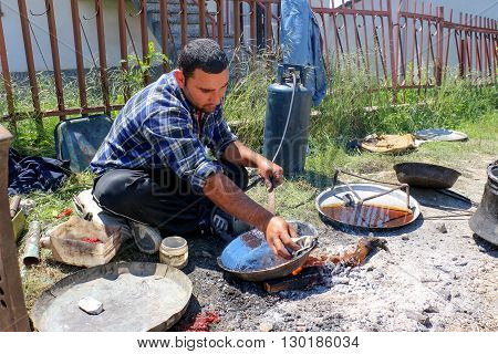 RESEN MACEDONIA. MAY 18 2016- Young traveling artisan retinning old copper dish in village of Carev DvorResen Macedonia