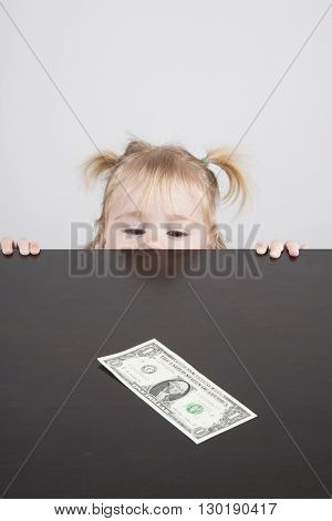 portrait of blonde caucasian baby nineteen month age with pigtails chubby face yellow shirt looking at dollar banknote on brown table vertical