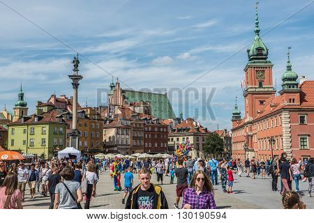 WARSAW POLAND - AUGUST 1 2015. People walks on a Castle Square on the Old Town of Warsaw among King Sigismund III Vasa Column and Royal Castle on photo