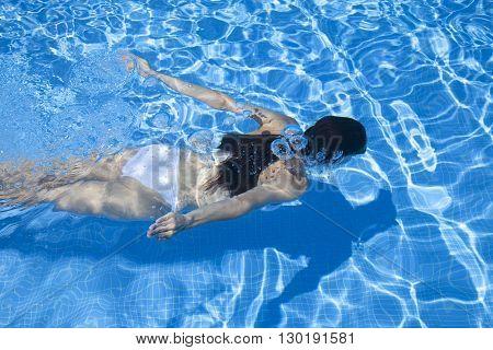 woman with white bikini swimming in a blue pool