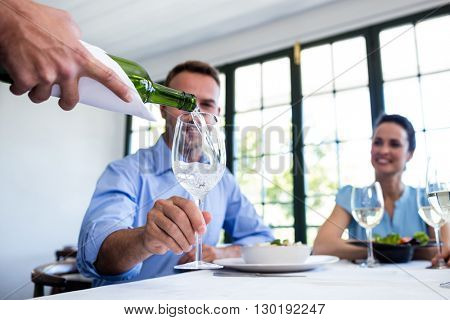 Waiter serving wine to group of friends while having lunch in a restaurant