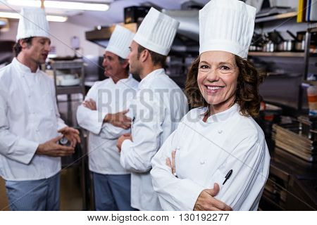 Portrait of smiling chef in commercial kitchen and thee chefs discussing In background
