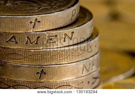 British pound coins stacked and showing Amen with Christian cross symbols