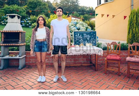 Young couple standing in front of barbecue and table with food in a outdoors summer party