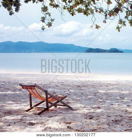 Deckchair in the shade of  tree, beach.
