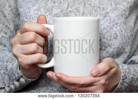 Girl is holding white cup in hands. White mug in woman's hands. Mockup for designs.