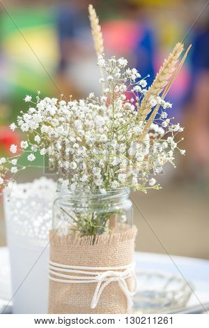 Flowers in mason jar with rope lace at an outdoors celebration