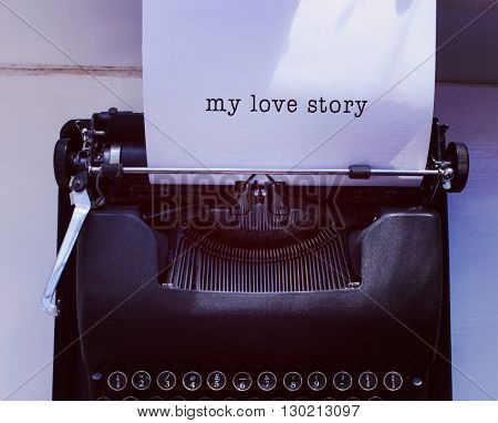 My love story message on a white background against womans hand typing on typewriter