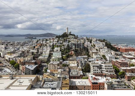 San Francisco, California, USA - April 23, 2016:  Growing clouds over San Francisco Bay, Coit Tower and the North Beach Neighborhood.