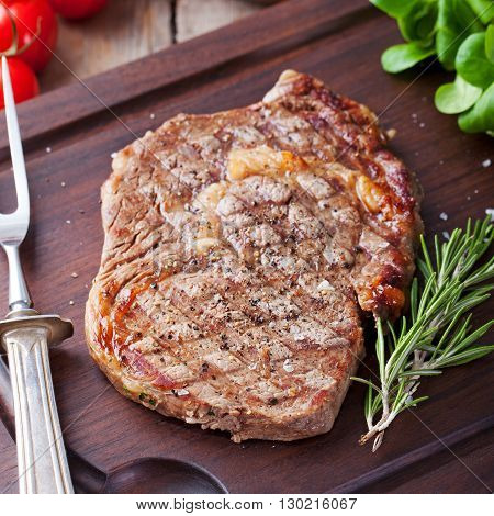 Beef steak with cherry tomato and rosmary on a dark cutting board Wooden background