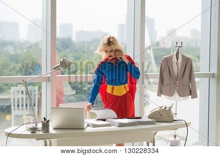 Powerful superwoman talking on phone and working with documents  in office