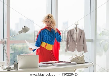 Angry superwoman reading document when negotiating by phone