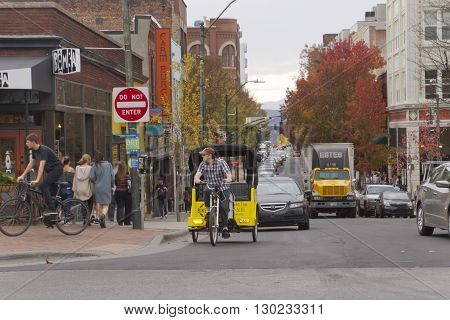 Asheville,North Carolina, USA - November 6, 2015: Busy downtown Asheville around Rush Hour with tourists and street traffic inlcuding a bicycle taxi on a cloudy day