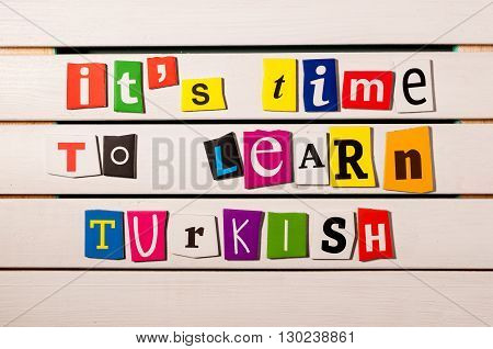 It's time to learn Turkish - written with color magazine letter clippings on wooden board. Concept  image.