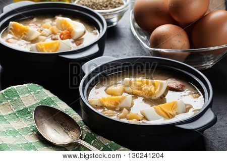 The sour soup made of rye flour with eggs on dish poster