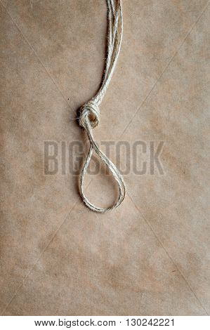 concept hangman's knot on kraft paper backgroun close up top view