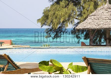 Summer holiday swimming pool resort with deckchairs against of blue ocean in sunlight