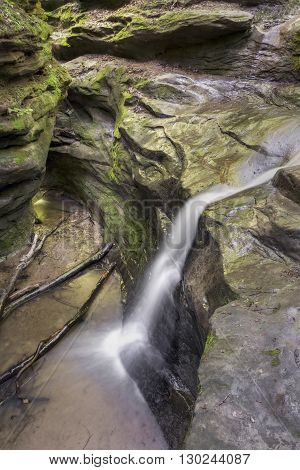 Water streams down the steep rocky sides of a deep chasm in Indiana's Turkey Run State Park.