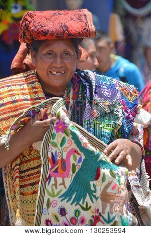 CHICHICASTENANGO GUSTEMALA APRIL 29 2016: Portrait of a Mayan woman saling table cloth. The Mayan people still make up a majority of the population in Guatemala,