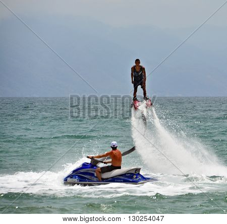 PUERTO VALLARTA MEXICO MAY 11 2016: Young man make flybording, Flyboard rider stands on a board connected by a long hose to a watercraft.