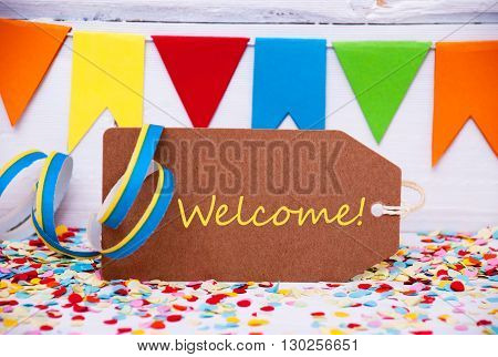 Label With English Text Welcome. Party Decoration Like Streamer, Confetti And Bunting Flags. White Wooden Background With Vintage, Retro Or Rustic Syle