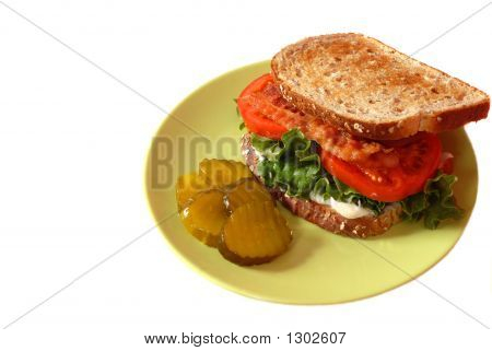 A Bacon, Lettuce And Tomato Sandwich With Pickles Isolated On Wh