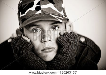 Young Boy Pouting While Holding Face In Gloves