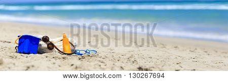 beach bag, suncream, kids toys on the beach, wide panorama