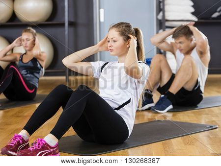 Woman With Friends Doing Situps In Gym