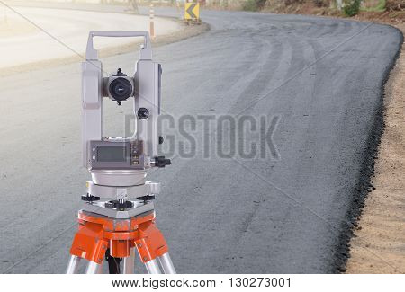 Survey equipment theodolite on a tripod. with road under construction background poster
