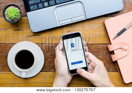 CHIANG MAITHAILAND - FEB 072016 : Man holding a iPhone 6s with Outlook application.Outlook is used for emails and also personal management of information.