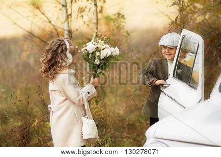 boy and girl on a village road in the car in a coat met in the autumn forest in the afternoon
