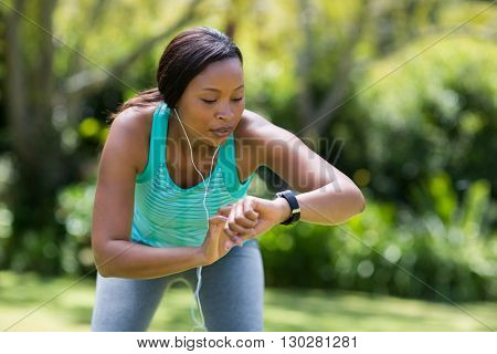 Woman looking her watch at park