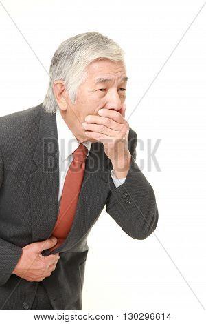 portrait of senior Japanese businessman feels like vomiting on white background