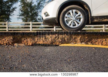 A car on crack of asphalt road after earthquake