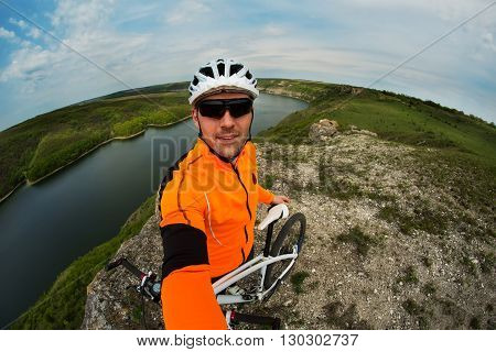 Cyclist in Orange Wear Riding the Bike Down Rocky Hill under River. Travel Concept poster