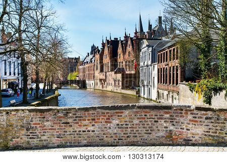 Bruges, Belgium - April 10 2016: Scenic cityscape with houses, part of bridge and Green canal Groenerei in Bruges, Belgium