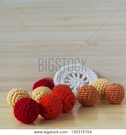 Red, orange and yellow crochet beads and white vintage elements of Irish crochet. Cotton yarn for knitting, crochet. Crochet doilies, crochet pattern coasters on bamboo background