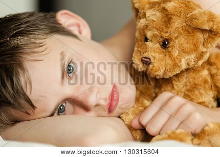 Teenage Boy Snuggling On Bed With Brown Teddy Bear