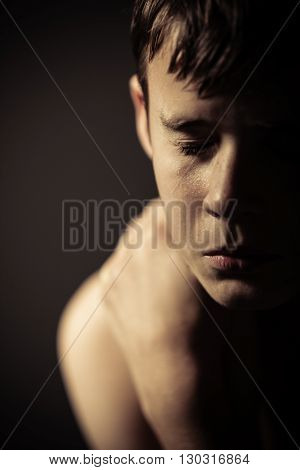 Shirtless Teenage Boy With Eyes Closed In Studio