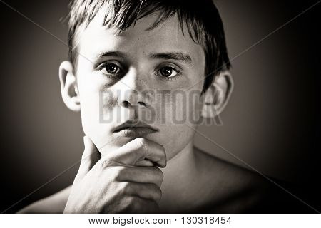 Serious Teenage Boy With Hand Resting On Chin