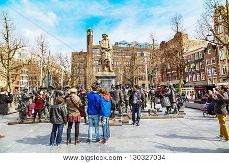 Amsterdam, Netherlands - March 31, 2016: Tourists posing for photo near Night Watch by Rembrandt in Rembrandtplein, Amsterdam, Netherlands