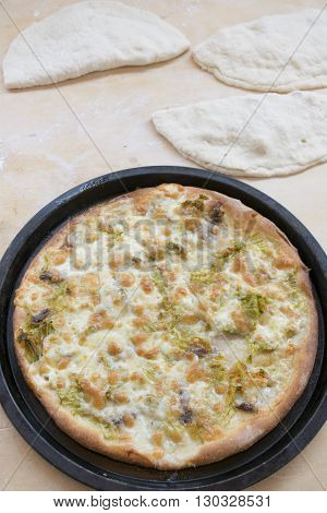boiling handcfraft pizza with zucchini flowers and mozzarella just taken out of the oven