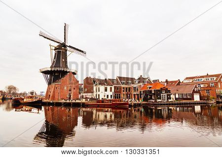 Haarlem, Netherlands - April 2, 2016: Picturesque morning landscape with the windmill and traditional houses Haarlem Holland